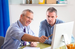 Photo of patient and doctor discussing information on a doctors' computer screen