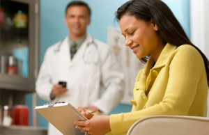 Photo of patient writing a list when meeting with her doctor